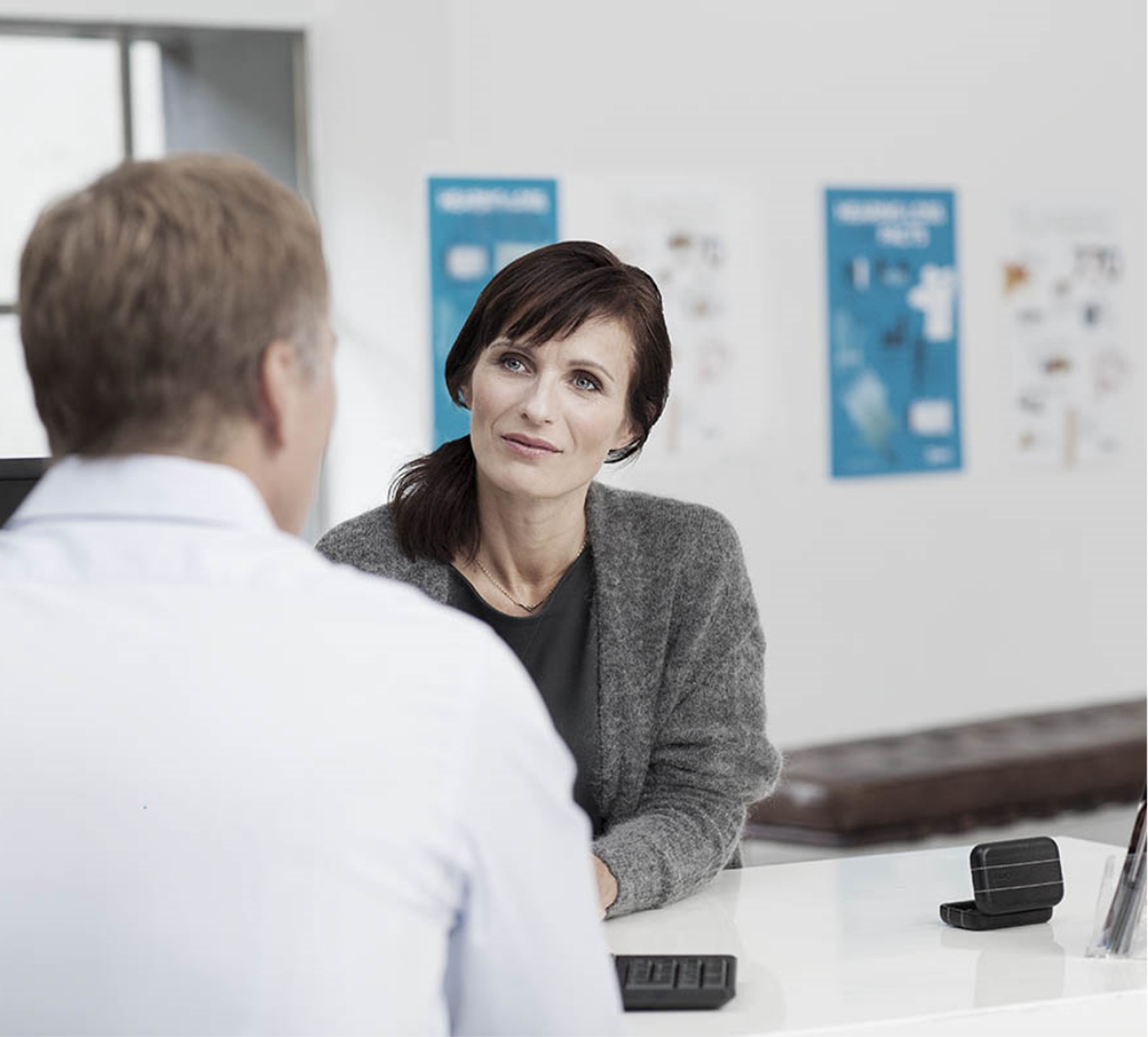 Woman sitting across table interviewing man