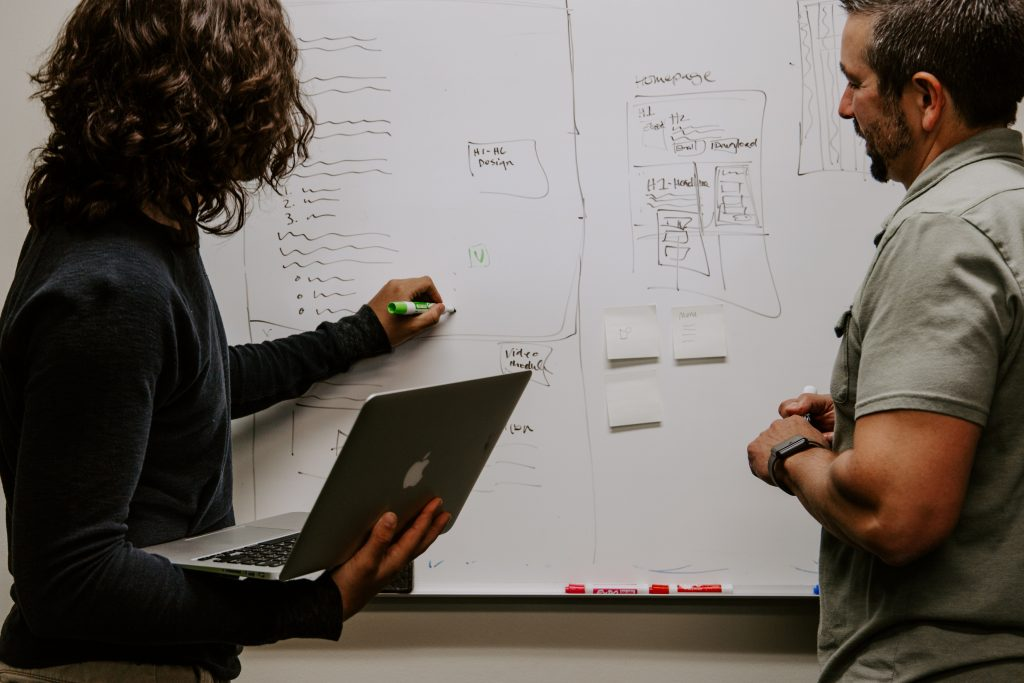 Woman at whiteboard diagramming design of homepage to man