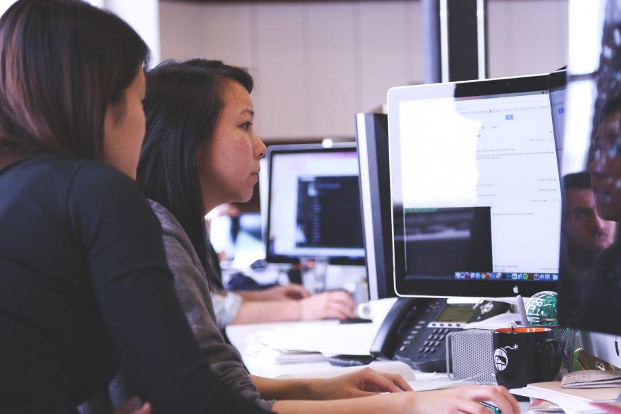 Zwei Frauen vor einem Computer beim Programmieren während eines Hackathons