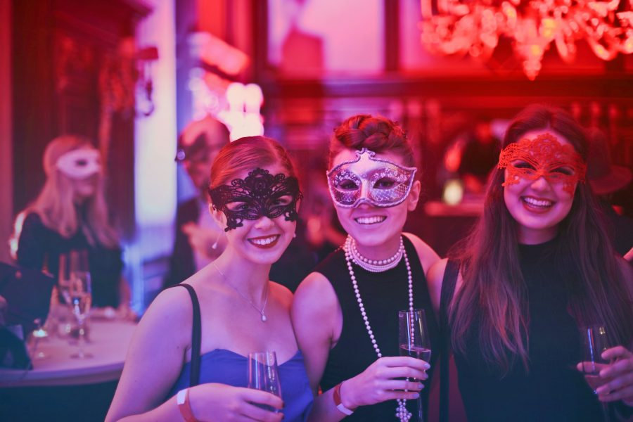 Women with masks at a themed event.